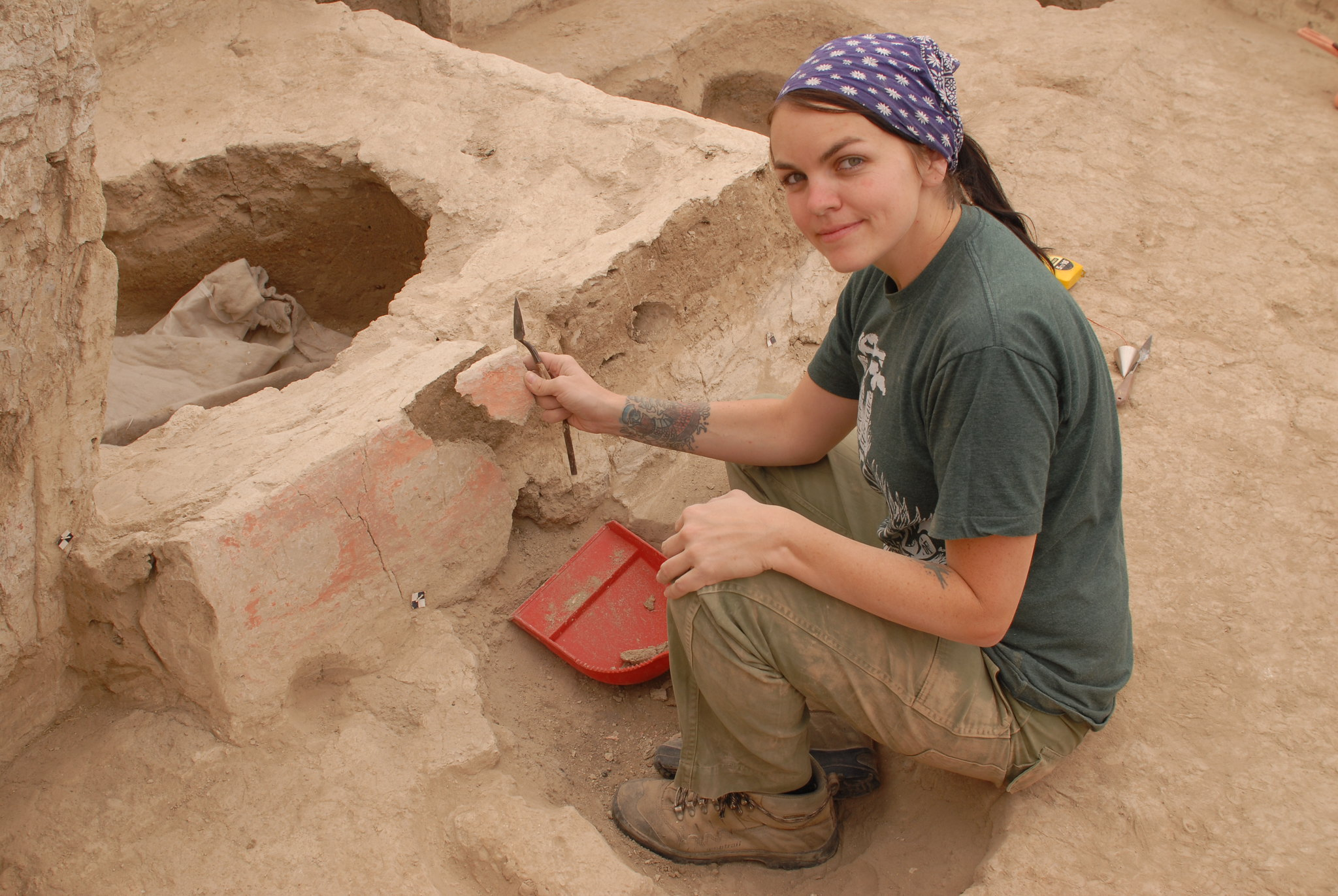 A woman kneels and holds a piece of stone at an archeological site