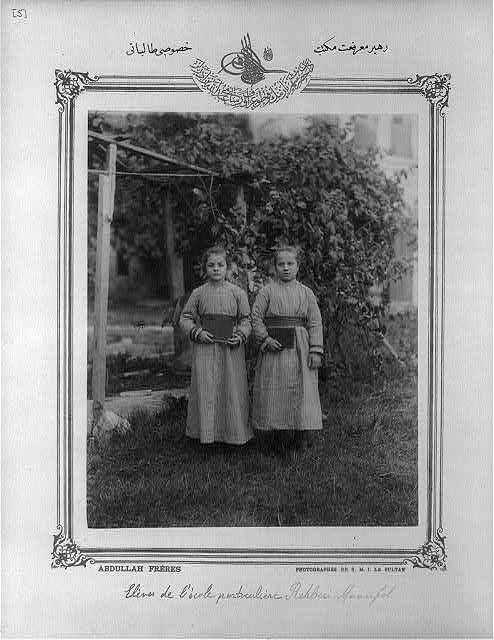 Black and white photograph of two girls in dresses standing in front of a tree
