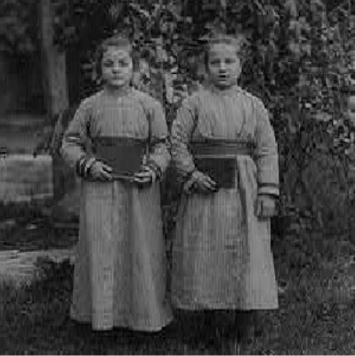 Detail: Black and white photograph of two girls in dresses standing in front of a tree