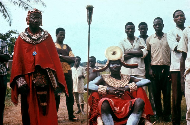 """Imaged titled """"Chief (Seated) and Sub-Chief of the Basengeles in Ceremonial Clothes"""" taken by John Ellington, undated.  It shows two men dressed in ceremonial clothing made of red robes and collars and cuffs made with what appears to be seashells.  They are flanked by men dressed in plain clothes."""