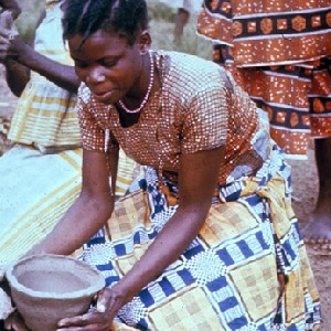 "Image from the collection titled ""Making Pottery at Kwilu"" taken by Robert E. Smith in the 1960s.  It shows a woman kneeling over a clay bowl she is sculpting with her hands."