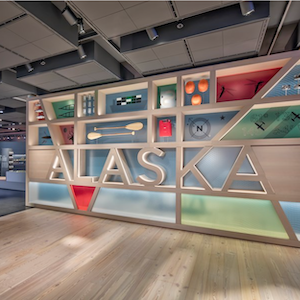 Museum exhibit showing Alaska in text with artifacts surrounding it.