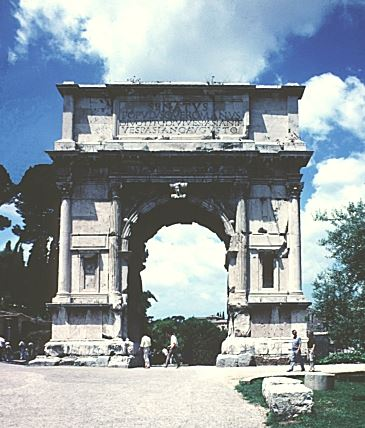 Image shows the Arch of Titus from outside the Forum which features sculptures dedicated to Titus' conquest of Judea during the years 66-70.