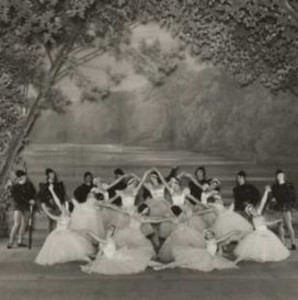 Black and white photograph of ballet dancers on stage performing Swan Lake. Several are in the front with white outfits, and are framed by a row of people in black.