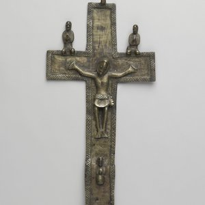 Copper-alloy cast crucifix, with two kneeling figures resting on bar above hands, with a third projecting below the central figure's feet.