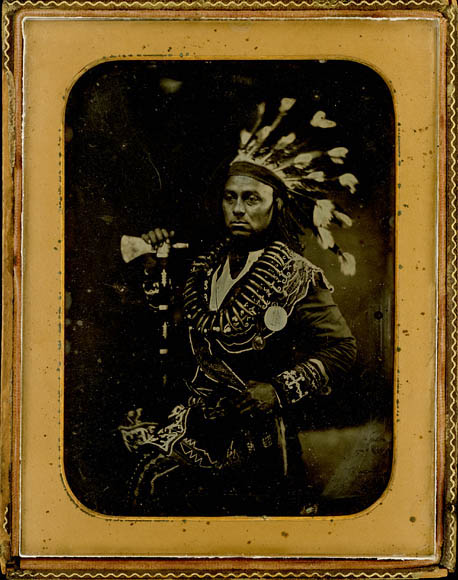 Photo of a man in a native american headress holding a hatchet
