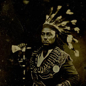 Thumbnail of a man in a native american headress holding a hatchet