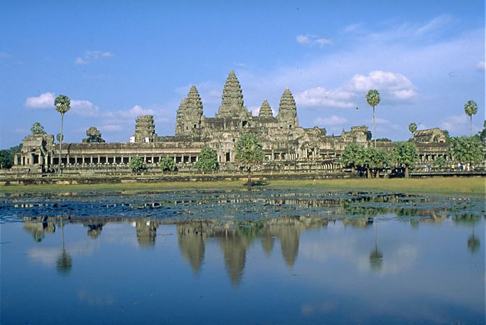 The image shows a pnaoramic view of Angkor Wat from the water reflecting the stone towers