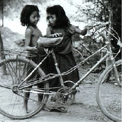 """The image is titled on the site as """"Children contend with a too-big bicycle, Pre Umbel"""" taken in 1991.  It is a black and white photograph showing too girls holding up a bicycle, unable to climb onto it."""