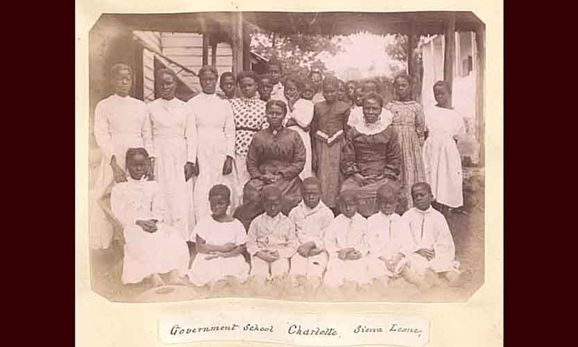 Pupils and their teachers all gathered in a group outside of their school in Charlotte, Sierra Leone in 1870. The younger children are all wearing white and are sitting on the ground in the front. The older students are wearing different colors and standing up behind the younger ones. The two female teachers are seated in chairs in the middle in between the students.