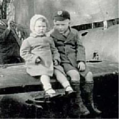 Detail of a photograph showing two children sitting on the wing of a crashed German fighter plane.
