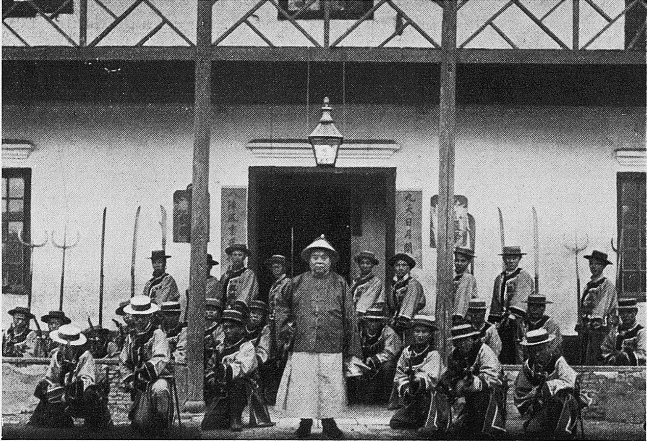 Photograph of about 20 soldiers posing in front of a building
