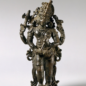 Bronze sculpture of Shiva standing with a head dress.
