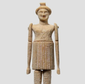 Image of clay figure of a woman with an ill defined face and long arms. It appears to be wearing a skirt.