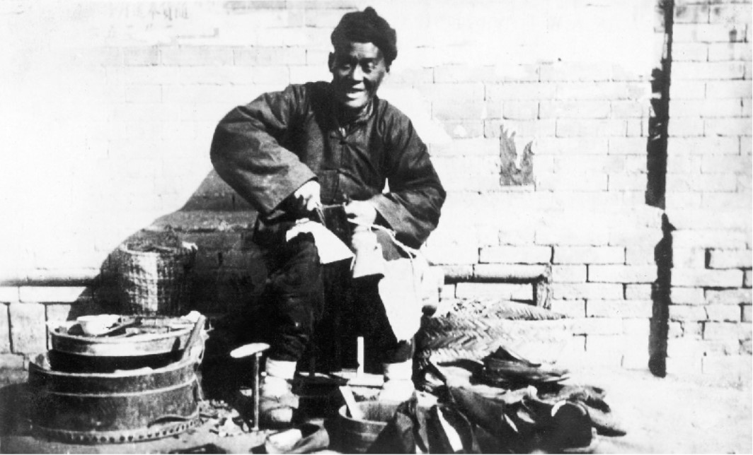 A Chinese cobbler sitting by the roadside with a pile of shoes