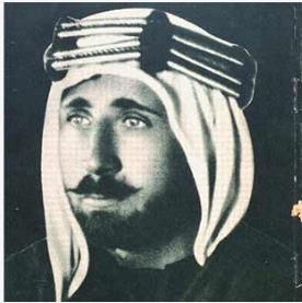 Black and white photo of a man in profile with a bead and mushtash, wearing a keffiyeh