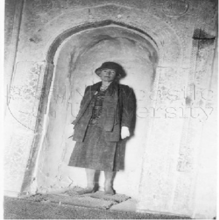 Gertrude Bell standing in a mosque's decorated arch