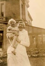 "Photo titled ""Happy Together"" from about 1930 showing a nurse holding a toddler."