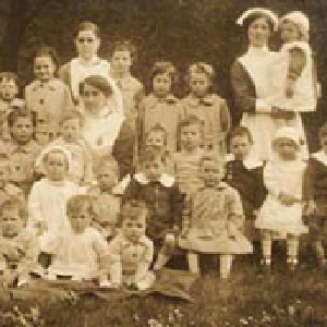 """Detail of a1919 photo titled """"Group Photo St. Deny's Home for Toddlers"""" showing a group of young children and a nurse."""