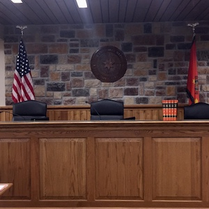 Image shows a judicial bench from the Cherokee Nation. Three chairs and two flags US and Cherokee are behind it.