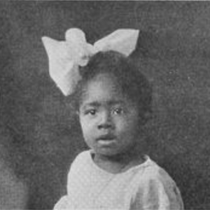 Photo of young girl with a bow in her hair.