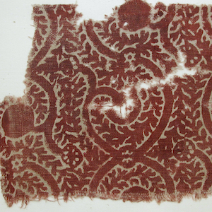 Red-brown textile with a looping tendril pattern