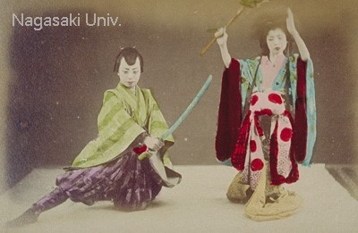 Two young women dance dressed as a woman and a man. The woman dressed as a man is a warrior with haori, hakama and a wooden sword. The other woman wears an courtesan costume and holds a stick to compete with the woman dressed as a man.