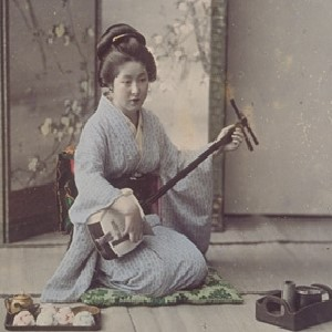 A woman dressed in a kimono and hair in Japanese style sits in a room playing a shamisen. A tray with a tea set and a tobacco tray are placed next to her, and a screen is placed at her back.