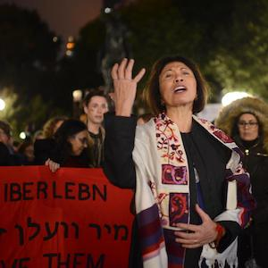 Thumbnail photo of a woman speaking with a banner in the background