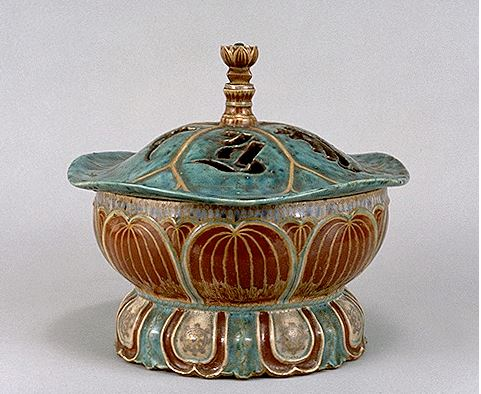 """The image is of a Ko-Kiyomizu Lotus-shaped incense burner from the museum's collections.  The bowl is re with a flower shaped lid and gold decoration. The museum describes it as """"The forms and motifs of this incense burner are rich in Buddhist imagery. The body of this burner represents a lotus seed, its lid a lotus leaf, and its foot a lotus flower. The lid is decorated with an openwork Sanskrit letter symbolizing the deity Thousand-Armed Kannon""""."""