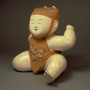 "The image is of ""Child with Fox Mask; Gosho Doll"" from the museum's collections.  It is a small, white porcelain figure of a child wearing a textile decorated with flowers.  A separate image of the doll on the site shows a fox mask for it to wear."