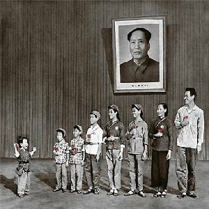 People of various ages standing in front of a portrait of Mao