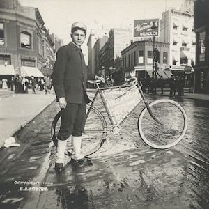 Thumbnail of boy posing with bicycle on a city street