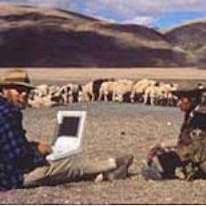 Picture of man sitting in front of landscape with a white laptop on his lap, next to a man in traditional dress. Behind them is a herd of animals.