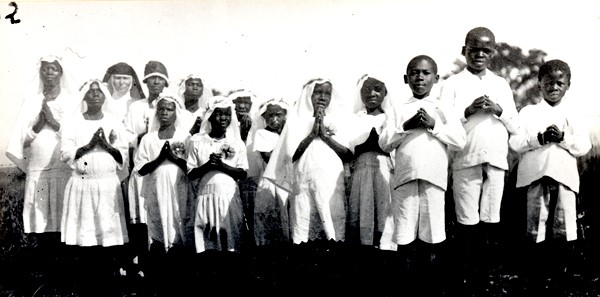 "Image from the collection titled ""First Catholic Communicants"" from 1931.  Its shows a group of 13 children and one nun posing for a picture to celebrate their first communion."