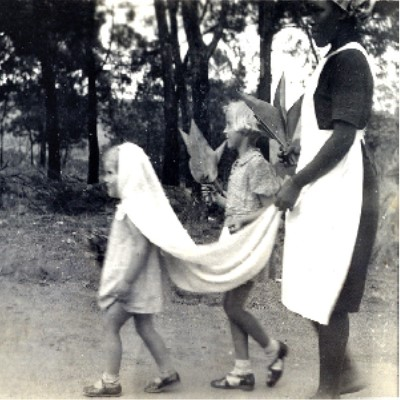 """Image from the collection titled """"Lady in Waiting"""" from the 1930s-1940s.  Its shows two children and their nanny walking.  The youngest child is walking in front with a cloth on her head and the nanny carrying the end like a wedding veil."""