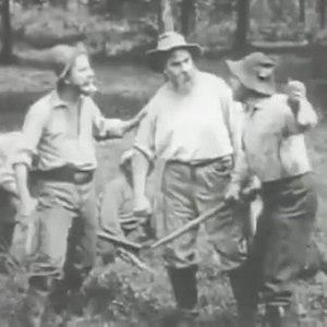 Film still shows three men talking in a field