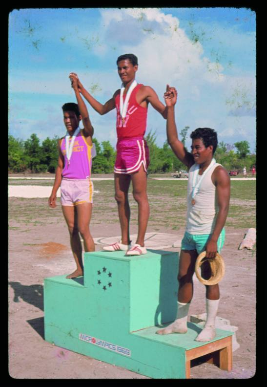 The image is from the 1969 Micronesian Olympics showing three young men standing on a podium holding hands and raising their arms.  They are wearing medals.