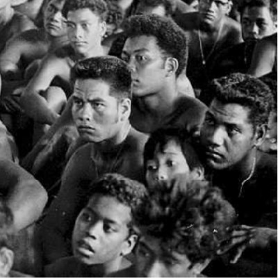 "The image is titled ""Outer Islands High School students"".  It shows a group of boys sitting on the floor in a crowd."