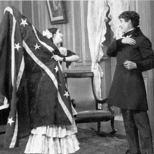 Film still image showing a man and a woman holding a flag