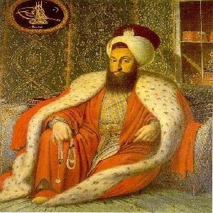 The portrait of Selim III 1789-1807, showing Selim dressed in red robes sitting against some pillows