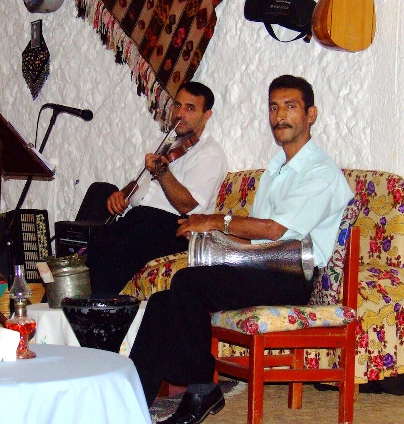 Two men sitting, one has a stringed instrument and one has a drum.