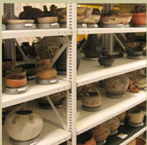 Color image of shelving with various artifacts, most of which are clay bowls or vessels