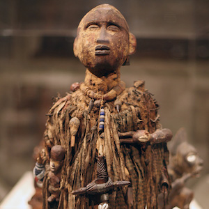 Wooden male figure decorated with pigment, nails, cloth, beads, shells, arrows, leather, nuts, twine