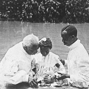 Thumbnail of two men baptizing a girl in a river
