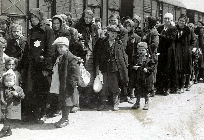 A line of women and children wait by a train
