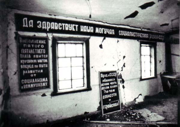 Black and white photograph of interior barrack ruins with visible propaganda slogans