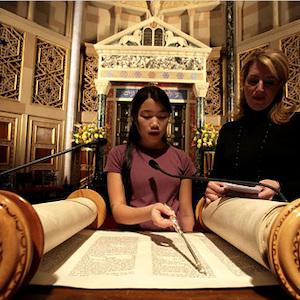 Thumbnail of girl reading from Torah