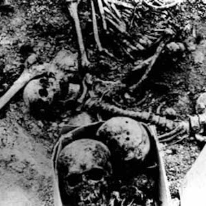 Black and white photograph of unearthed human skulls and bones