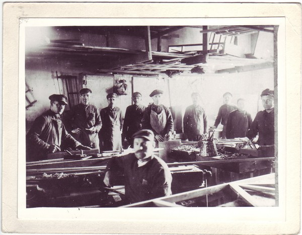 Black and white photograph of a group of men working in the wood shop at the Svirskie camps